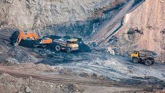 Crawler excavator and dump trucks are working in a quarry